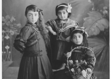 Three young Armenian girls, one holding a basket of roses. (From left to right: Rebecca H. Hazarian, Yevnige Hazarian, Araxi Hazarian; daughters of Hagop Hazarian). Constantinople, Ottoman Empire (now Istanbul, Turkey), ca. 1912.