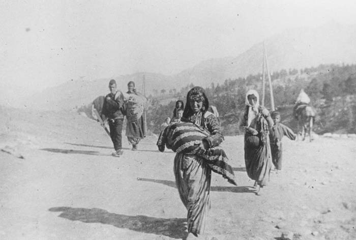 A small group of Armenian deportees walking through the Taurus Mountain region, carrying bundles. A woman in the foreground carries a child. Ottoman Empire, ca. November 1915. Photograph taken by Armin T. Wegner. Wegner served as a nurse with the German Sanitary Corps. In 1915 and 1916, Wegner traveled throughout the Ottoman Empire and documented atrocities carried out against the Armenians.