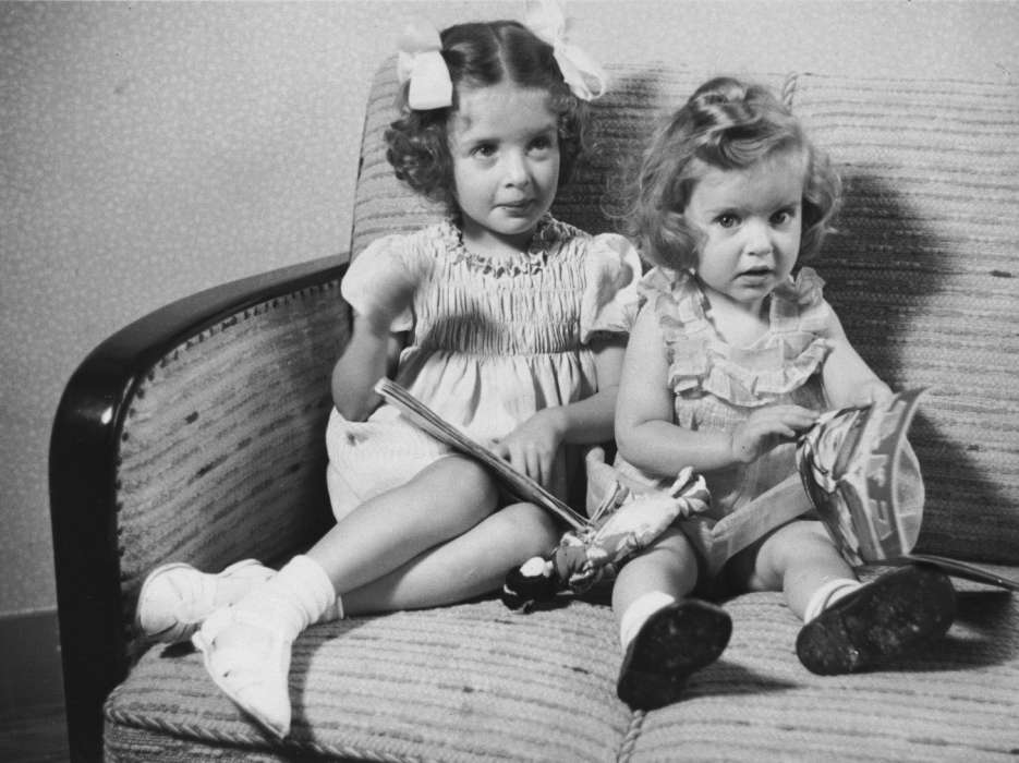 Jewish sisters, Eva and Leana Münzer, sit on a sofa in their home in The Hague.