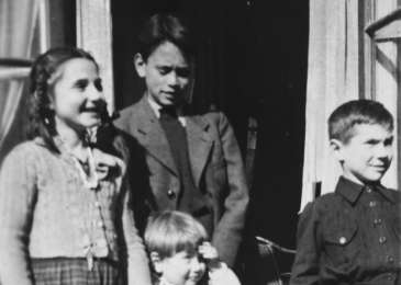 Alfred Münzer, a Jewish child who is living in hiding, poses with his foster brother and two neighbors.