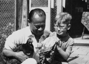 Alfred Münzer and Tole Madna sit outside holding chickens during a postwar visit.
