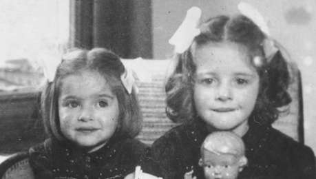 Jewish sisters pose with their dolls in their home in The Hague. Pictured are Eva and Leana Münzer.