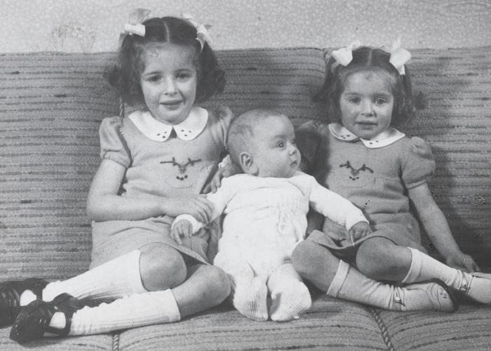 Jewish siblings pose on a sofa in their home in The Hague. Pictured are Eva, Alfred, and Leana Münzer.  Both later perished in Auschwitz.