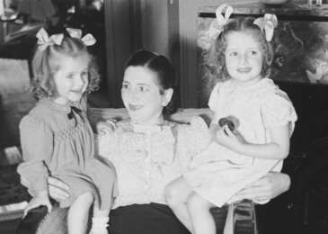Gitel Münzer sits on an armchair with her daughters, Eva and Leana.