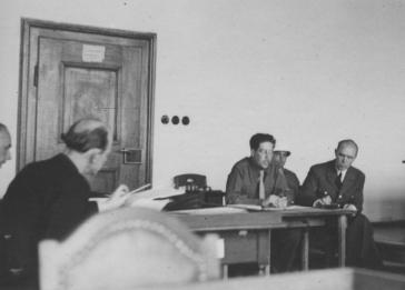 Field Marshall Albert von Kesselring testifies at the IMT Nuremberg commission hearings investigating indicted Nazi organizations. Kesselring sits at the table at right, next to the interpreter, Gerd Schwab.
