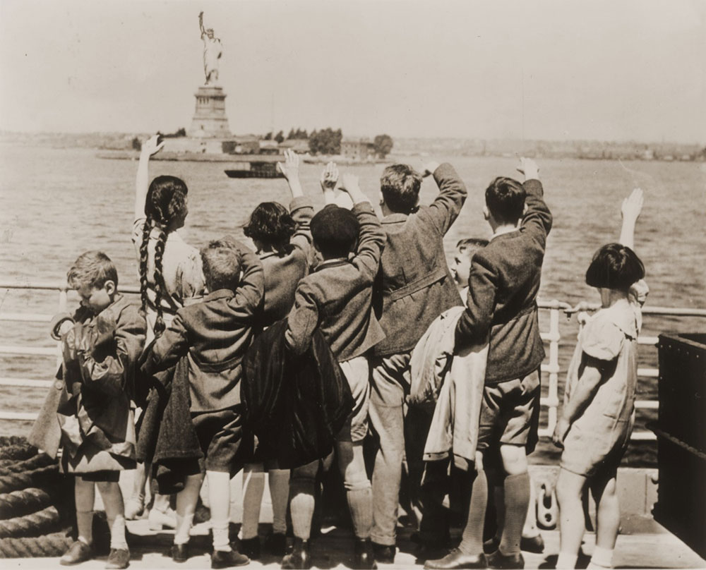 Austrian-Jewish refugee children wave at the Statue of Liberty as the SS President Harding steams into New York harbor.