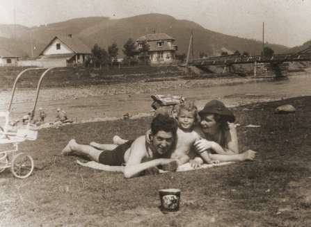 :	A Jewish couple sunbathes with their son on the beach in the resort town of Skole.