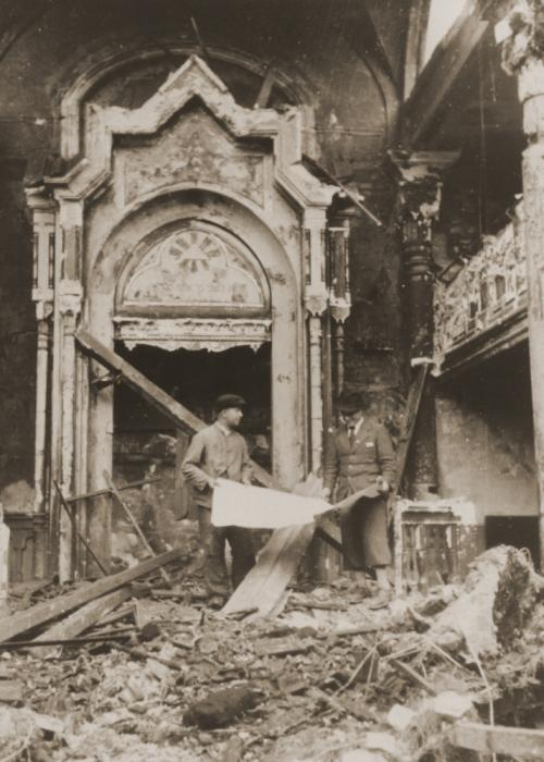 Standing amid the rubble and ashes, workers examine the blueprints of the Kaiser-Wilhelmstrasse synagogue, which was destroyed on Kristallnacht.