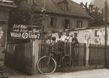 "Nazi Party supporters stand next to an election poster that reads: ""Adolf Hitler will provide work and bread! Elect List 2!' Posted on the wall at the right are posters urging women and workers to support the Nazis. Rosenheim, Germany, 1932."