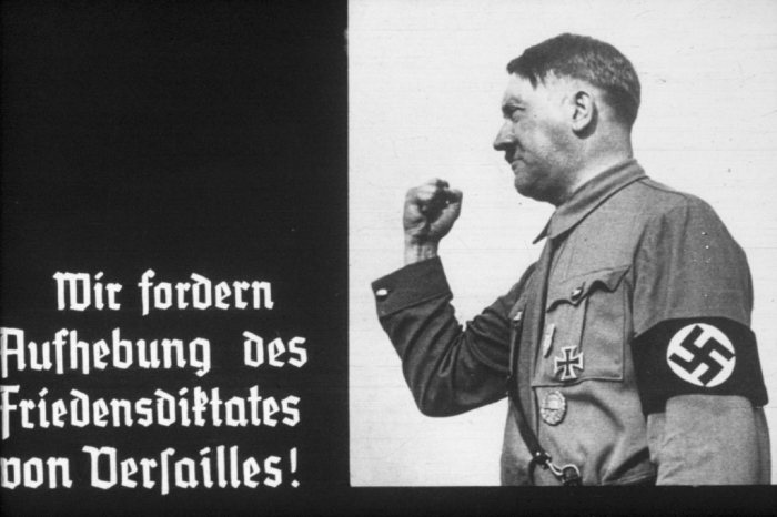 "Slide from a propaganda filmstrip titled <i>Overcoming Versailles</i>  produced for Hitler Youth groups. This  image of Hitler appears next to text which reads, in translation: ""We demand the repeal of the dictated peace of Versailles."""