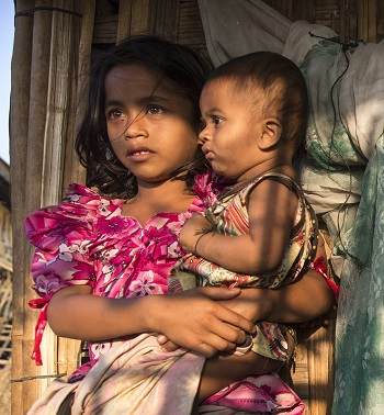 Rohingya children, displaced by violence, wait outside a makeshift shelter in March 2015.