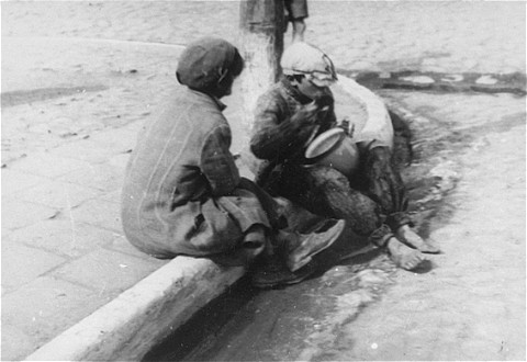 Two destitute children share a bowl of food on the streets of the Lodz ghetto.