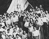 Jewish youth pose with a Zionist flag in Tradate, Italy, where they are awaiting an opportunity to immigrate to Palestine.