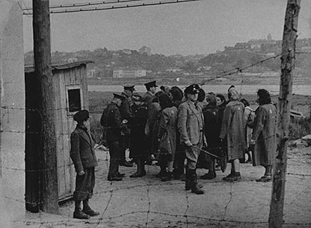 German and Lithuanian guards search Jewish women returning from forced labor outside the ghetto. Kovno, Lithuania, wartime.