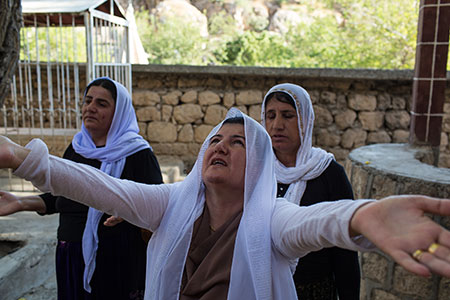 Yazidi women pray on the sacred grounds of Lalish in Iraq. The self-proclaimed Islamic State has committed genocide against the Yazidi minority in Iraq.