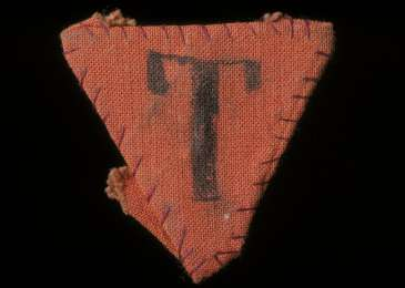 "Red triangle patch worn by Czech political prisoner Karel Bruml in Theresienstadt. The letter ""T"" stands for Tscheche (Czech) in German."