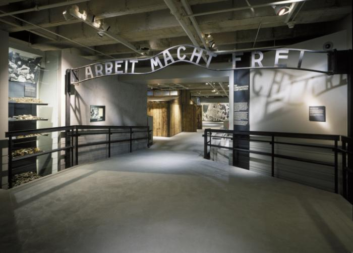 "Museum visitors pass under this gate, a cast taken from the original entrance to the Auschwitz death camp, inscribed with the ironic phrase Arbeit Macht Frei (""Work Makes One Free"")."