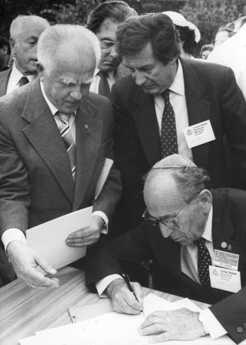Miles Lerman, representing the United States Holocaust Memorial Council, signs an agreement with the Main Commission for the Investigation of Nazi Crimes in Poland at the site of Belzec. Warsaw, Poland, 1987. <i>US Holocaust Memorial Museum, courtesy of Gustaw Russ</i>