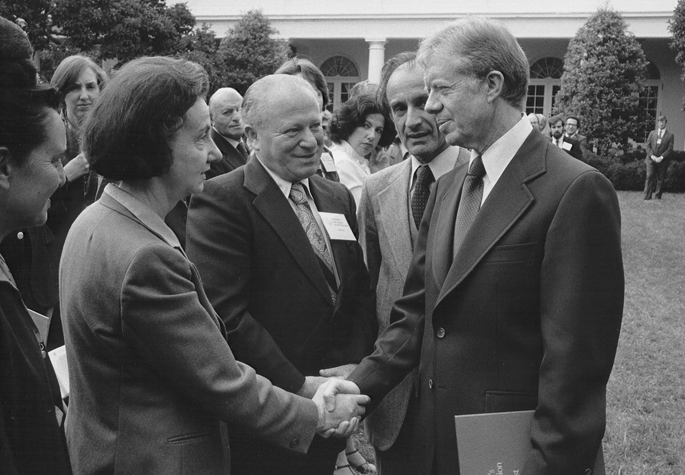 President Jimmy Carter shakes the hand of Vladka Meed during a ceremony in the White House Rose Garden, during which Elie Wiesel presented the report of the US Holocaust Commission.