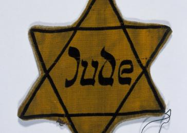 A yellow star of David marked with the German word for Jew worn by Fritz Glueckstein.