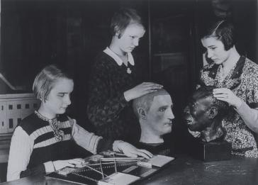Students at the Berlin School for the Blind examine racial head models circa 1935. Students were taught Gregor Mendel's principles of inheritance and the purported application of those laws to human heredity and principles of race. <i>Blinden-Museum an der Johann-August-Zeune-Schule fur Blinde, Berlin</i>