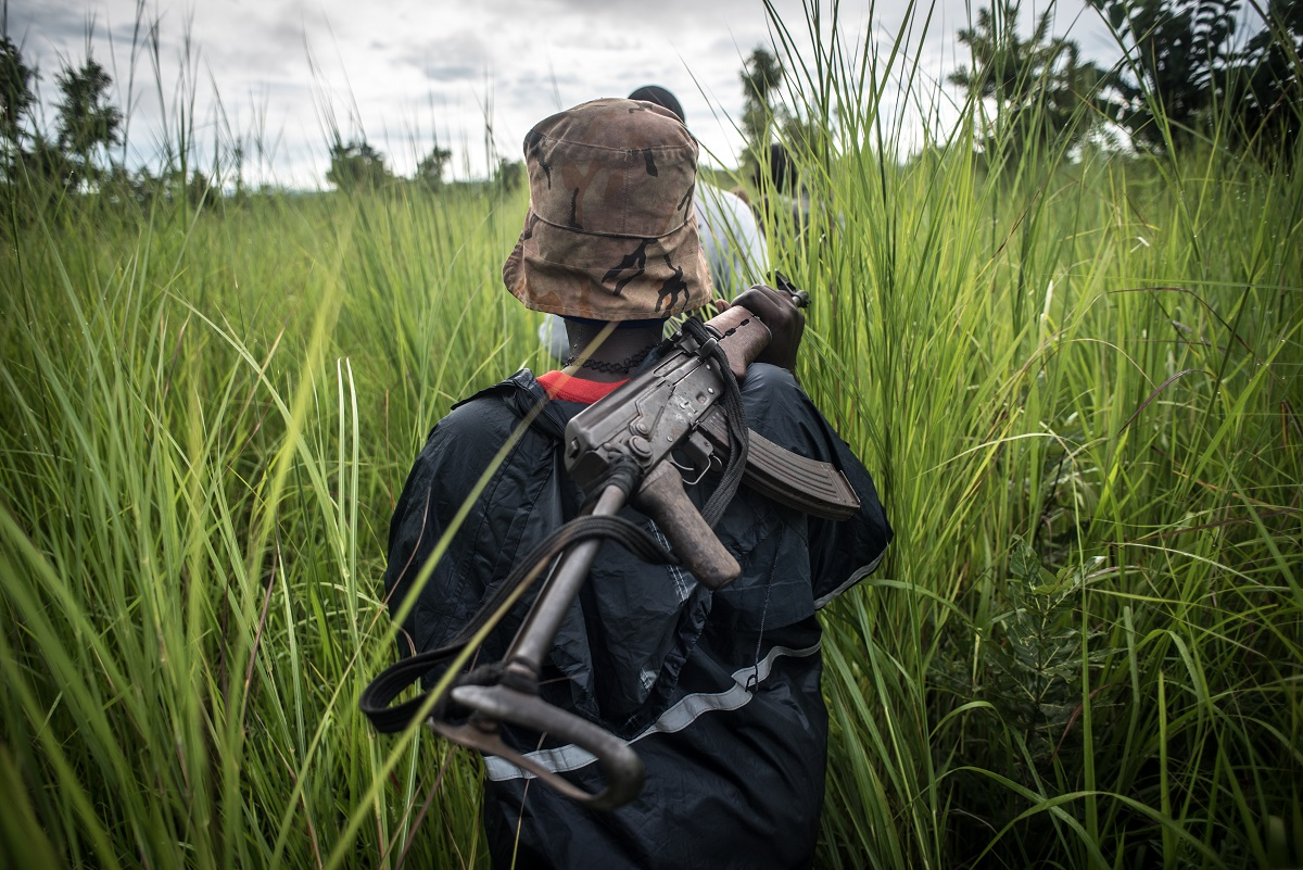 A SPLA-In Opposition soldier walks with her weapon through the elephant grass in rebel-held Magwi county of South Sudan's Eastern Equatoria state on August 28, 2017.