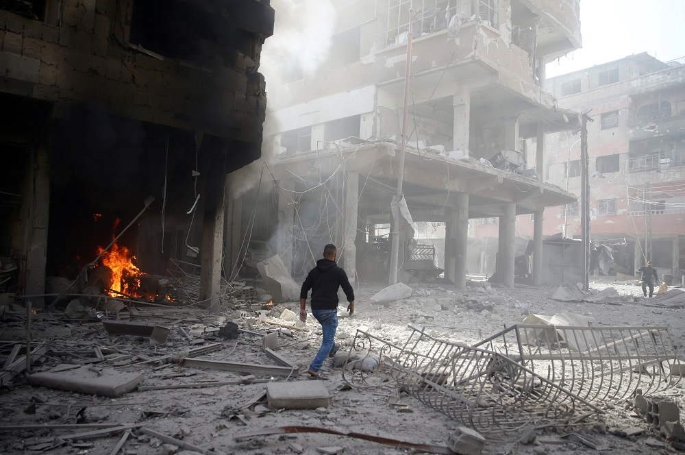 A man walks on rubble at a damaged site after an air strike on February 9, 2018, in the besieged town of Douma in the Eastern Ghouta area of Damascus, Syria.