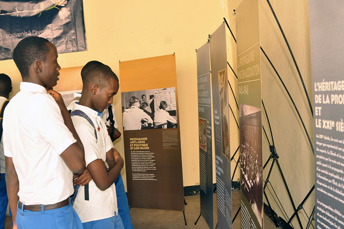 Students visit a State of Deception poster exhibition.