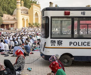 In July 2015, outside the Id Kah Mosque in the ancient Silk Road trade town of Kashgar, Uyghur men and women pray during Eid al-Fitr, a joyous Muslim holiday that marks the end of Ramadan. Police vehicles and security line the public square in Xinjiang, China.