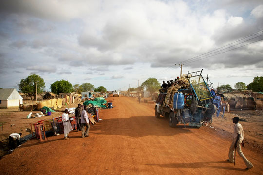UN peacekeepers pass through streets lined with looted items awaiting collection in Abyei. UN Photo/Stuart Price/May 2011.