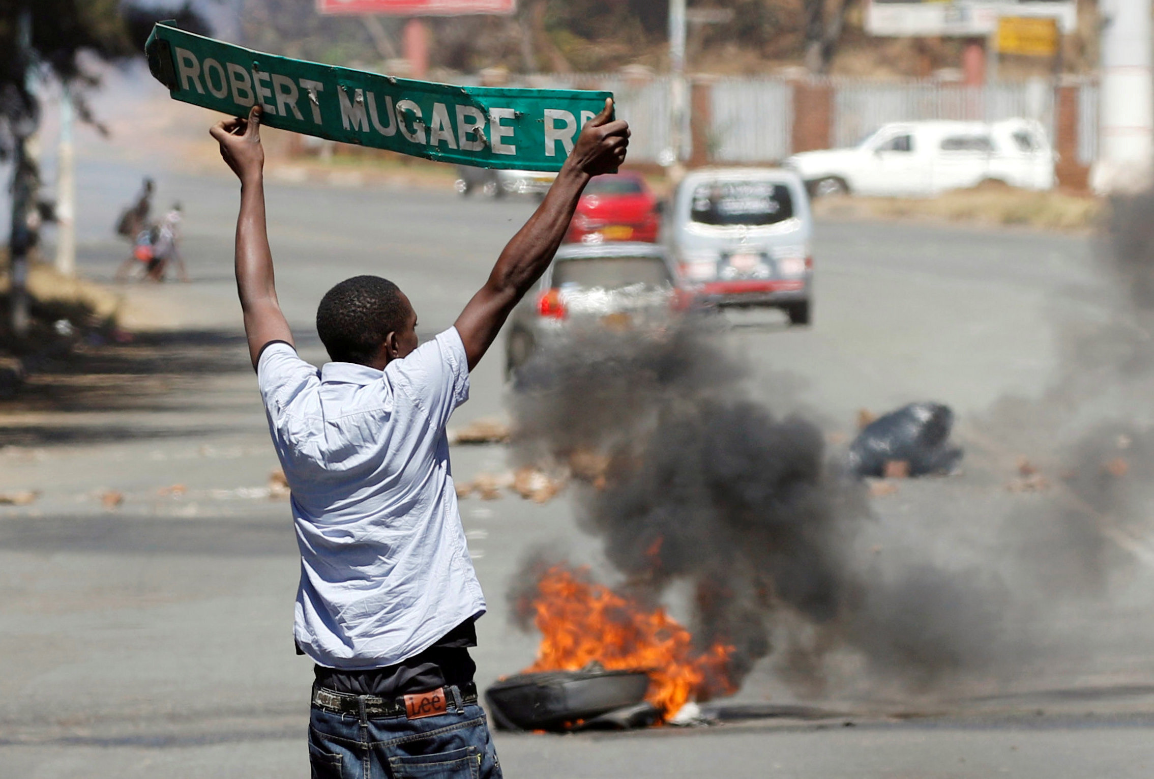 A man carries a street sign as opposition party supporters clash with police in Harare, Zimbabwe, August 26, 2016.