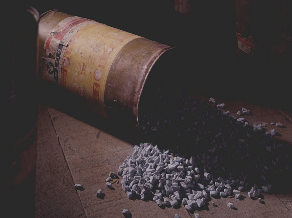A canister of Zyklon B gas crystals lies overturned on a table with some of its contents spilled.