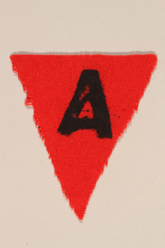 1989.295.1 front Unused red triangle concentration camp patch with an A found by US military aid worker