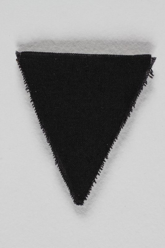 1989.295.11 front Unused black triangle concentration camp patch found by a US military aid worker