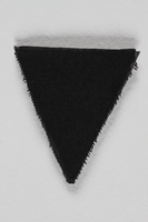 1989.295.11 front Unused black triangle concentration camp patch found by a US military aid worker  Click to enlarge