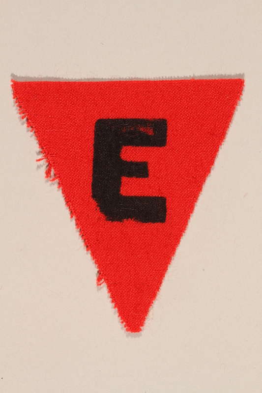 1989.295.2 front Unused red triangle concentration camp patch with an E found by a US military aid worker