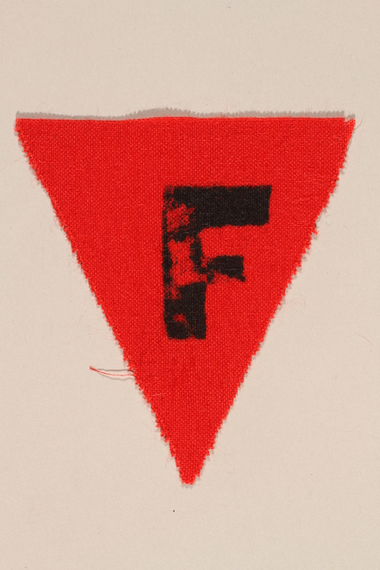 1989.295.3 front Unused red triangle concentration camp patch with an F found by a US military aid worker