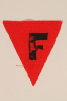 1989.295.3 front Unused red triangle concentration camp patch with an F found by a US military aid worker  Click to enlarge