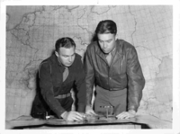 Sydney L. Burr (on left) studying a map Dachau at liberation; death train; SS bodies  Click to enlarge