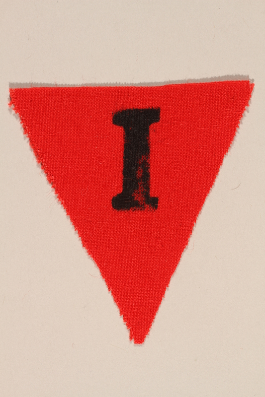 1989.295.4 front Unused red triangle concentration camp patch with an I found by a US military aid worker