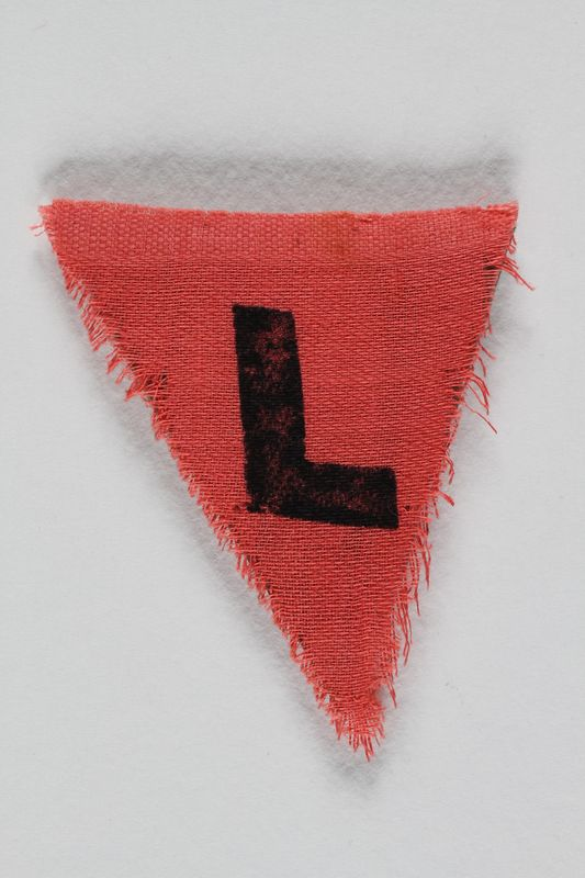 1989.295.5 front Unused red triangle concentration camp patch with an L found by a US military aid worker
