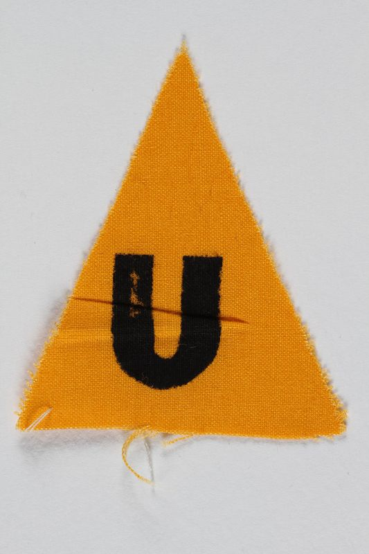 1989.295.6 front Unused yellow triangle concentration camp patch with a U found by a US military aid worker