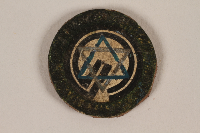 1995.89.1084 front Jewish Ghetto Police badge from the Kovno ghetto