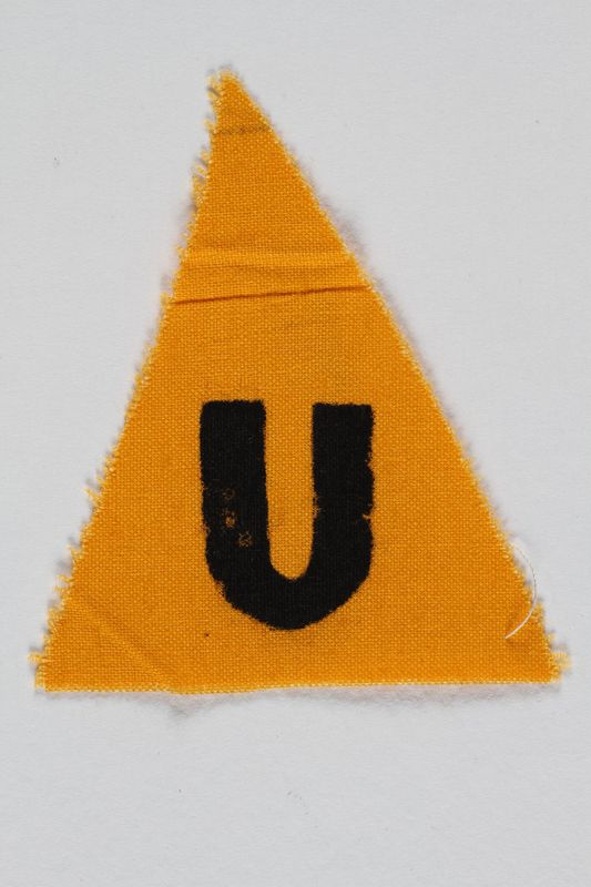 1989.295.8 front Unused yellow triangle concentration camp patch with a U found by a US military aid worker