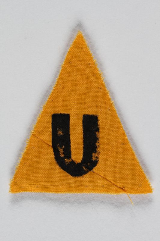 1989.295.9 front Unused yellow triangle concentration camp patch with a U found by a US military aid worker