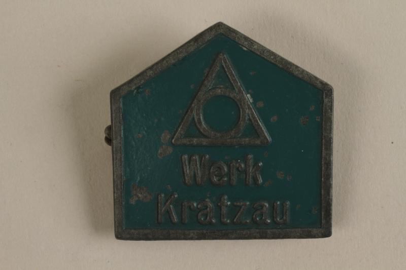1989.296.1 front Green metal Werk Kratzau labor camp badge worn by an inmate