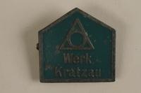 1989.296.1 front Green metal Werk Kratzau labor camp badge worn by an inmate  Click to enlarge