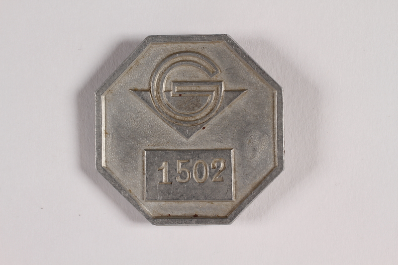 2014.426.2 front Metal pin badge with the letter G worn by a Polish Jewish woman living under a false identity