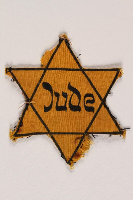 1989.303.55 front Star of David badge with Jude owned by Czech Jewish concentration camp prisoners