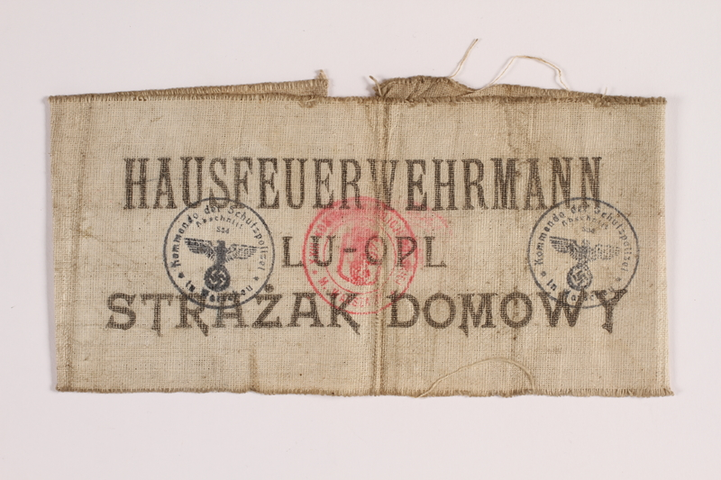 2014.450.3 front White cloth armband worn by a Roman Catholic Polish firefighter in Warsaw